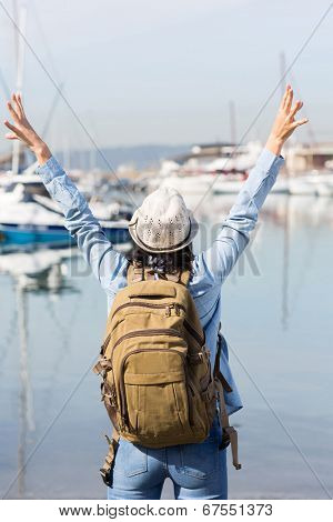back view of female tourist with arms up at the harbor