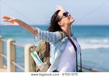 pretty tourist standing on pier with arms outstretched