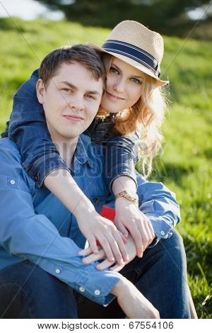 Happy young couple sitting in a park.