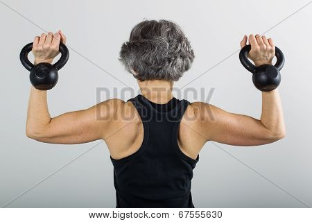 Middle Aged Female Sports Trainer With Kettle Bells