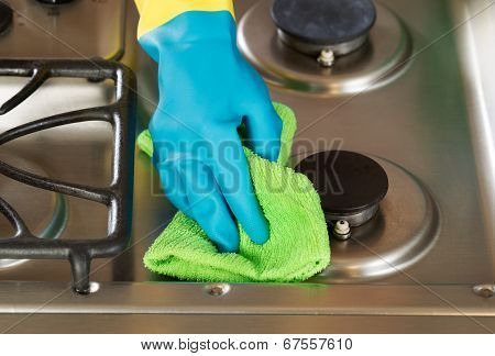 Gloved Hand Wiping Down Stove Top Range With Green Microfiber Rag