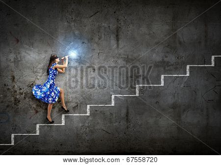 Young woman in blue dress playing fife and stepping the ladder