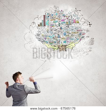Young businessman speaking in trumpet with business sketches on wall