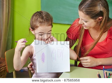 Proud girl showing her drawing to nursery teacher in kindergarten