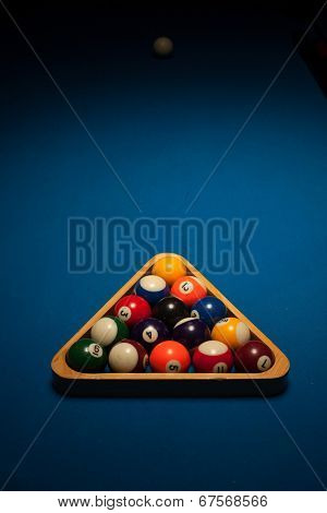 Racked set of numbered object pool balls in a triangular wooden rack ready for an eight-ball frame or game on a blue beize table with copyspace