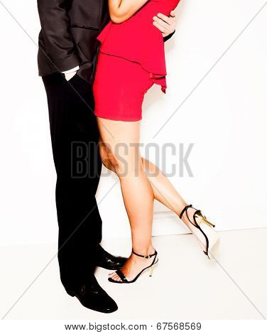 Seduction in the office as a businessman in a suit stands holding a sexy woman in a red dress and high heels in an intimate embrace, lower bodies isolated on white