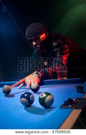 Trendy man in dark glasses and a cap playing pool lining up on the cue ball with his cue as he prepares to shoot in a dark pub or club