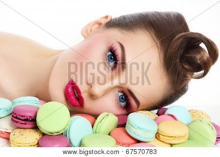 Portrait of young beautiful woman with colorful macaroons over white background
