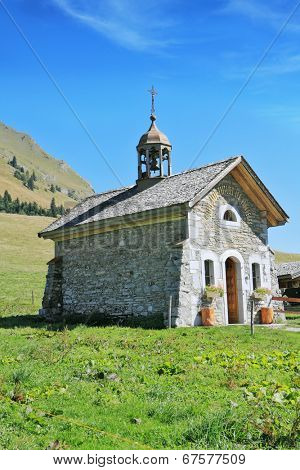 France, Haute Savoie. Adorable little chapel on the lawn in the mountains. Sunny spring day