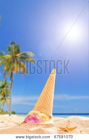 An ice cream melting in the sand on a tropical beach on sunny day
