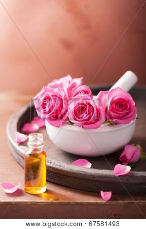 mortar with rose flowers and essential oil for aromatherapy and spa
