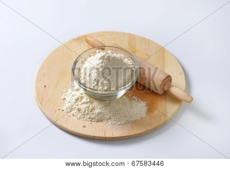 flour in the glass bowl, on the wooden cutting board with rolling pin