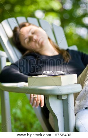 woman dosing off after reading a book