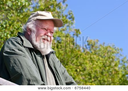 Senior man looking down with trees and sky behind