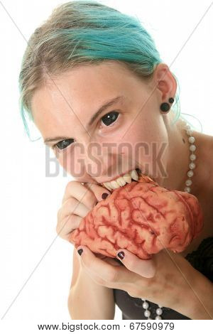 A young woman dressed as a Vampire - Zombie complete with black contacts and Vampire Fangs enjoys eating the brain of her latest victim. Isolated on white with room for your text