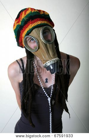 a girl in a gas mask wears her favorite Rastafarian style hat with built in Dred locks.