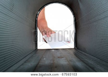 A Unique view of someone getting or placing mail in a mail box, shot from the Inside Out.