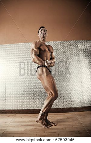 Attractive male body builder showing muscles