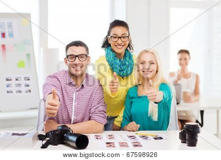 business, education, photography, office and startup concept - smiling creative team with printed photos working in office
