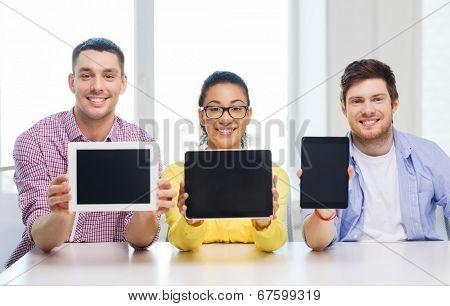 education, technology, business, startup and office concept - three smiling colleagues showing tablet pc blank screen