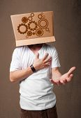 foto of spurs  - Young man standing and gesturing with a cardboard box on his head with spur wheels - JPG