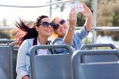 picture of two women taking cell phone  - two tourists taking a selfie with smart phone on an open top bus - JPG