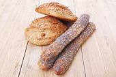 pic of baguette  - delicacy french rye breads and baguettes topped with sunflower and poppy seeds over wooden table - JPG