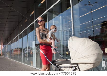 Trendy Mother And Baby Posing Near Showcase