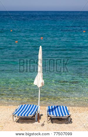 Sun Beds And Umbrellas On The Beach Of Mediterranean Sea (crete, Greece)