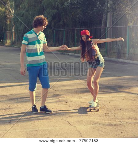Teen Boy Helping Teen Girl To Ride A Skateboard