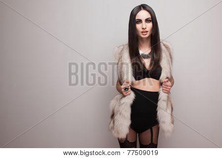 Fashionable Beautiful Model In Fur Coat And Black Stockings