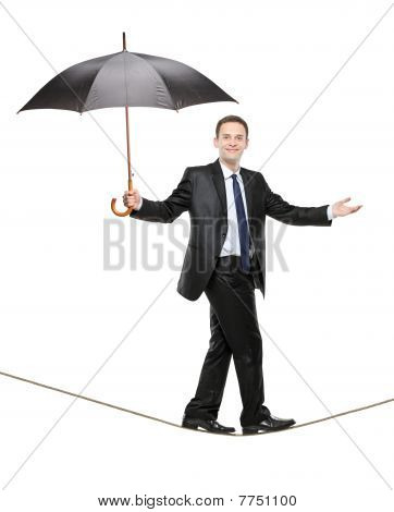 A perosn holding an umbrella and walking on a high tightrope