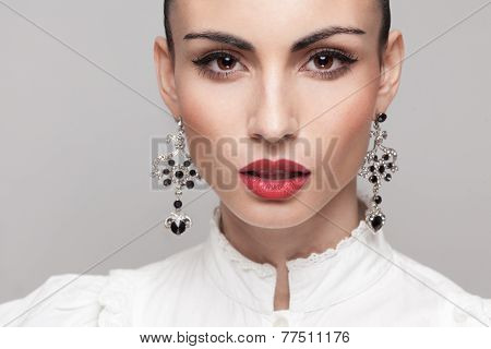 Headshot Of Fashionable Model With Perfect Makeup And Hairstyle. Red Lips, White Shirt. Big Earrings