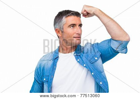 Man with grey hair tensing arm muscle on white background