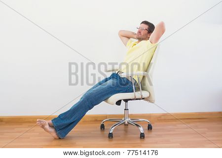 A man leaning back in swivel chair at home in the living room