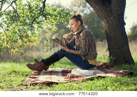 Romantic Portrait Of Reading Trendy Girl Sitting Beneath A Tree In The Evening