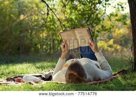 Lying Woman Reading A Book During A Relax In The Park.