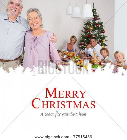 Grandparents standing by the dinner table against merry christmas