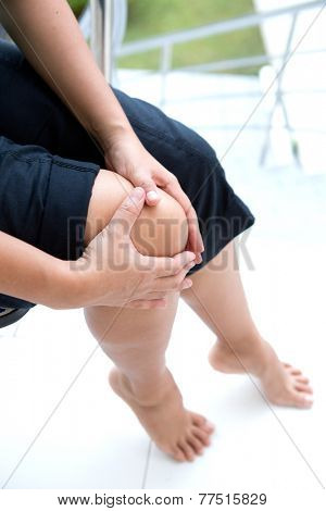 Woman holding right knee with both hands while sitting down to show pain in the knee area