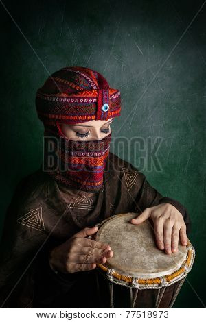 Woman In Turban Playing Drum