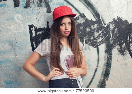 Trendy Beautiful Long Haired Yuong Model With Big Lips Posing On Graffiti Background. Blowing Bubble