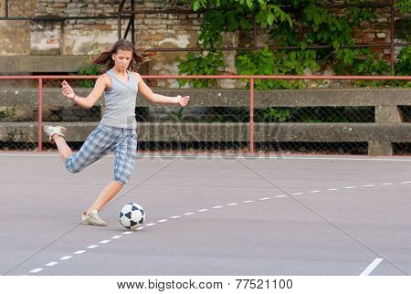 Pretty teenage girl playing football