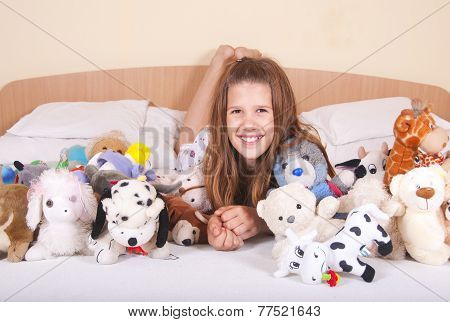 Girl in the bed with toys