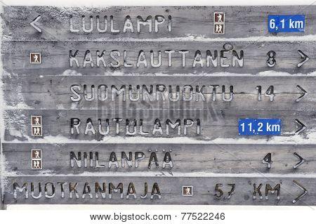 Wooden directions sign in winter in Finnish Lapland, Saariselka, Finland.