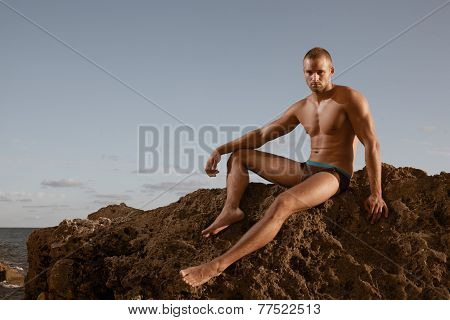 Very Muscular Handsome Sexy Guy Sitting On Rocky Beach, On Sky Background