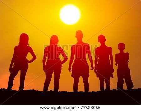 Silhouettes of boys and girls standing on the beach on sunny summer day