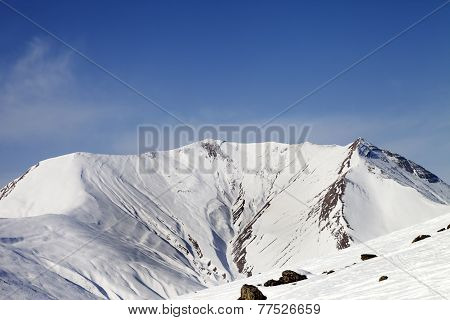 Off-piste Slope With Stones And Snowy Mountains