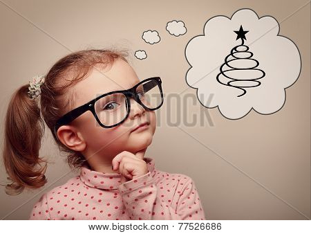 Cute Kid Girl In Glasses Thinking About Gifts And Fur Tree On Christmas Holiday