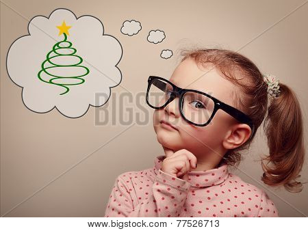 Cute Kid Girl In Glasses Thinking About Gift On Christmas Holiday