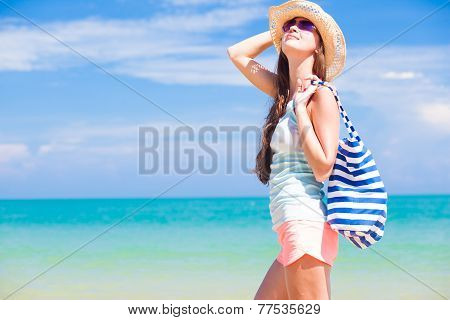 half face view of a fit young woman with stripy bag at tropical beach